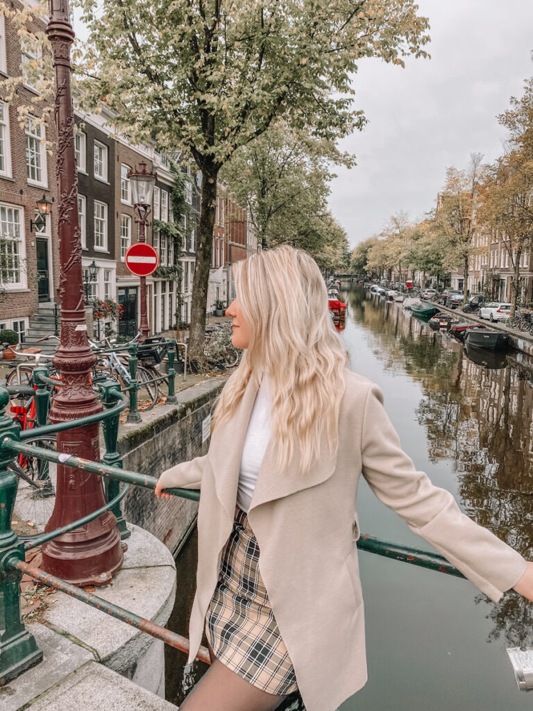 Girl standing infront of a canal in Amsterdam