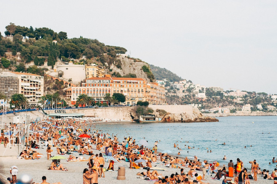 Nice beach with people on it and the buildings and cliffs in the distance
