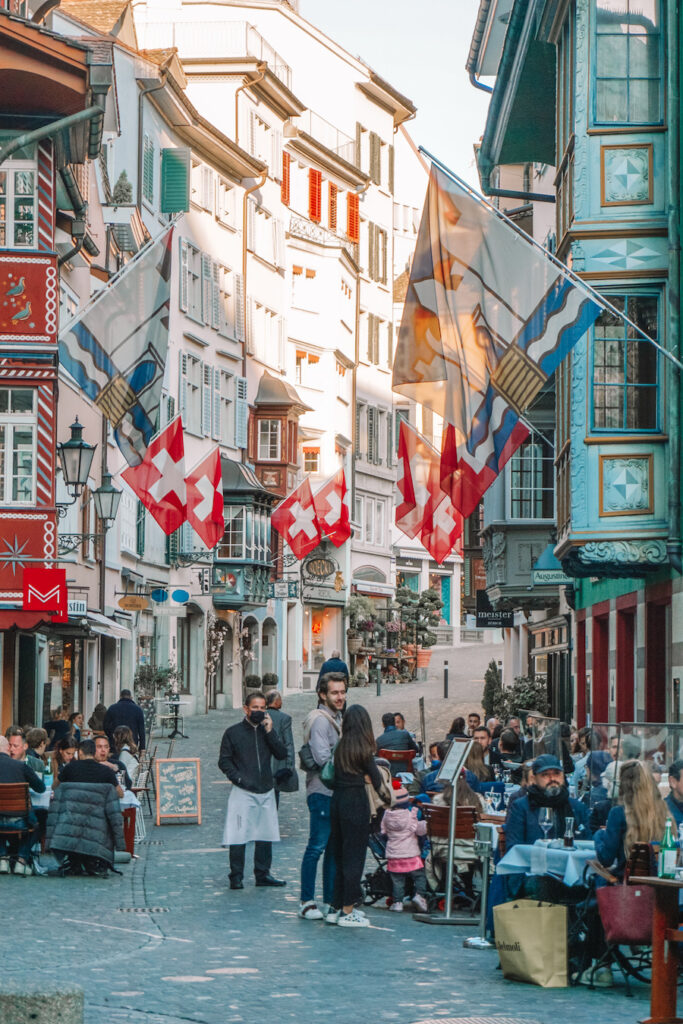 Zurich street view with cobblestone streets and Swiss flags on buildings