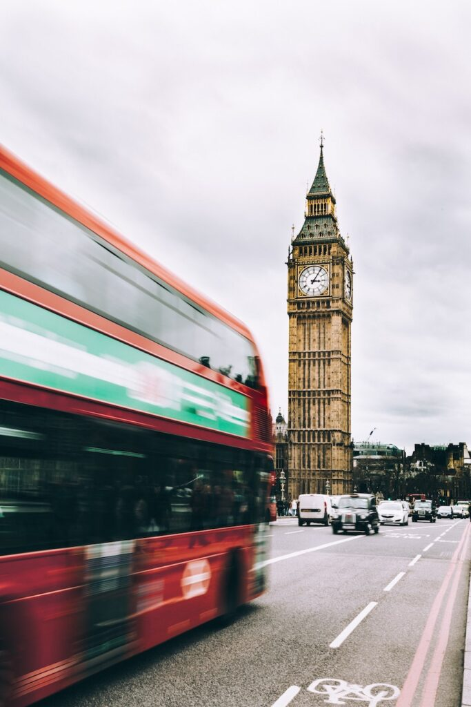 Big Ben with a red bus driving by