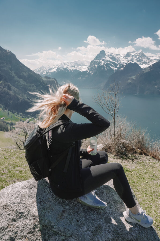 Girl sitting on a mountain overlooking the Swiss alps