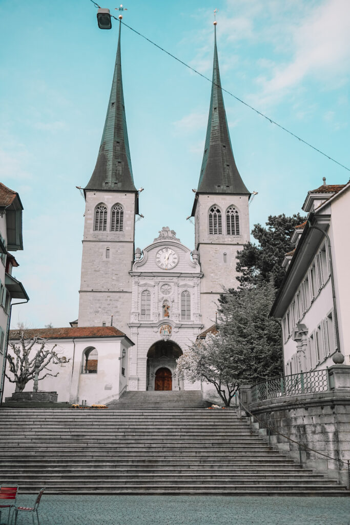 White stone church with green spires