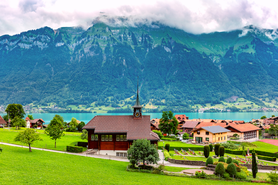 Panoramic view of swiss village Iseltwald with traditional wood church on the southern shore of Lake Brienz, Switzerland