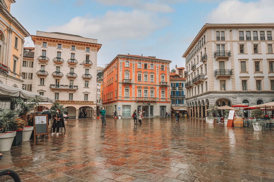 Big square in Lugano with restaurants and buildings surrounding