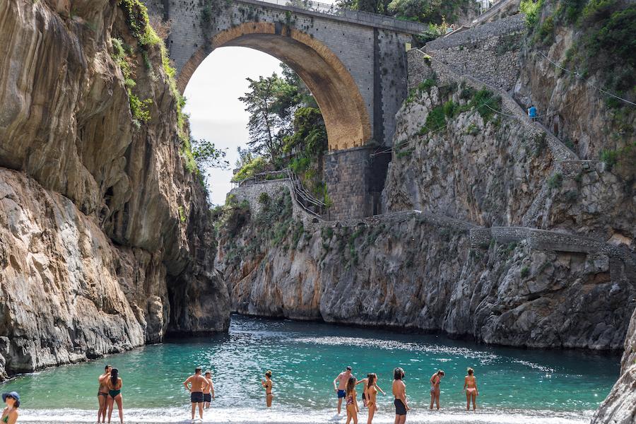 iordo di Furore beach. Furore Fjord, Amalfi Coast, Positano, Naples, Italy. May 2018 - Tourists standing at the beach and into the turquoise Mediterranean beach. The bridge over the fjord.