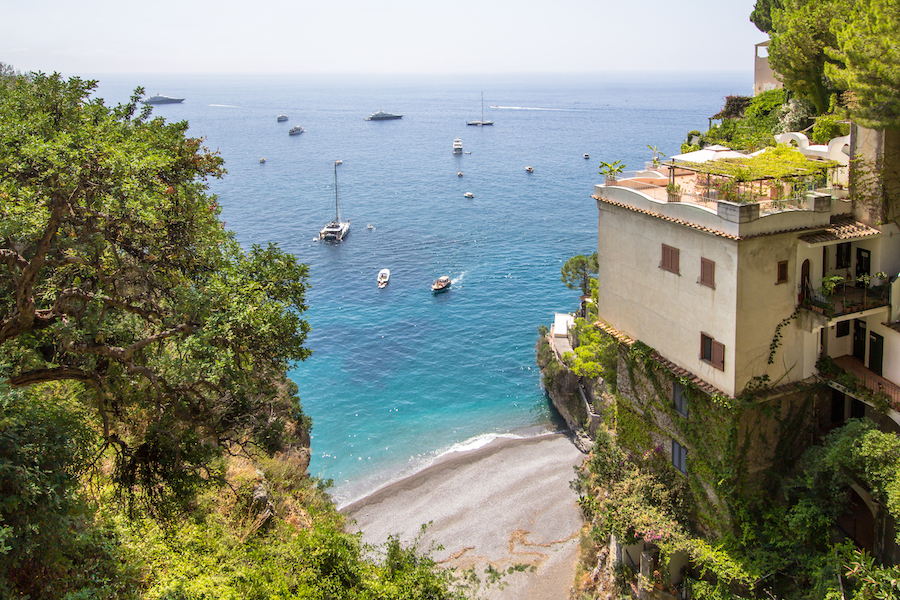 Top view to the little beach Spiaggia la Porta with the luxury yachts in Positano city, Amalfi coast, Italy