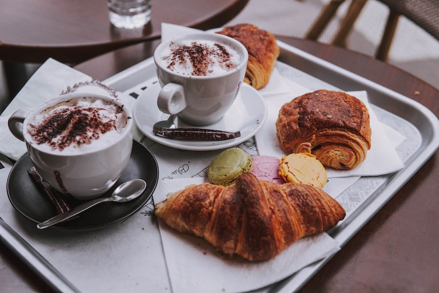 Two cappuccinos and pastries on a table in Paris