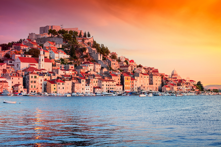 Sunset in old town of Sibenik, Croatia. Waterfront view with reflection
