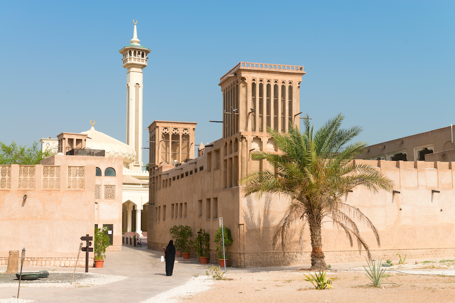 Woman in traditional muslim black dress in old arabic city district with mosque minaret on background