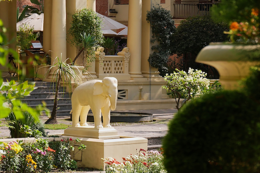 White colored elephant sculpture in the Garden of Dreams (also Garden of Six Seasons) in the center of Kathmandu, Nepal framed by plants. Focus on sculpture.